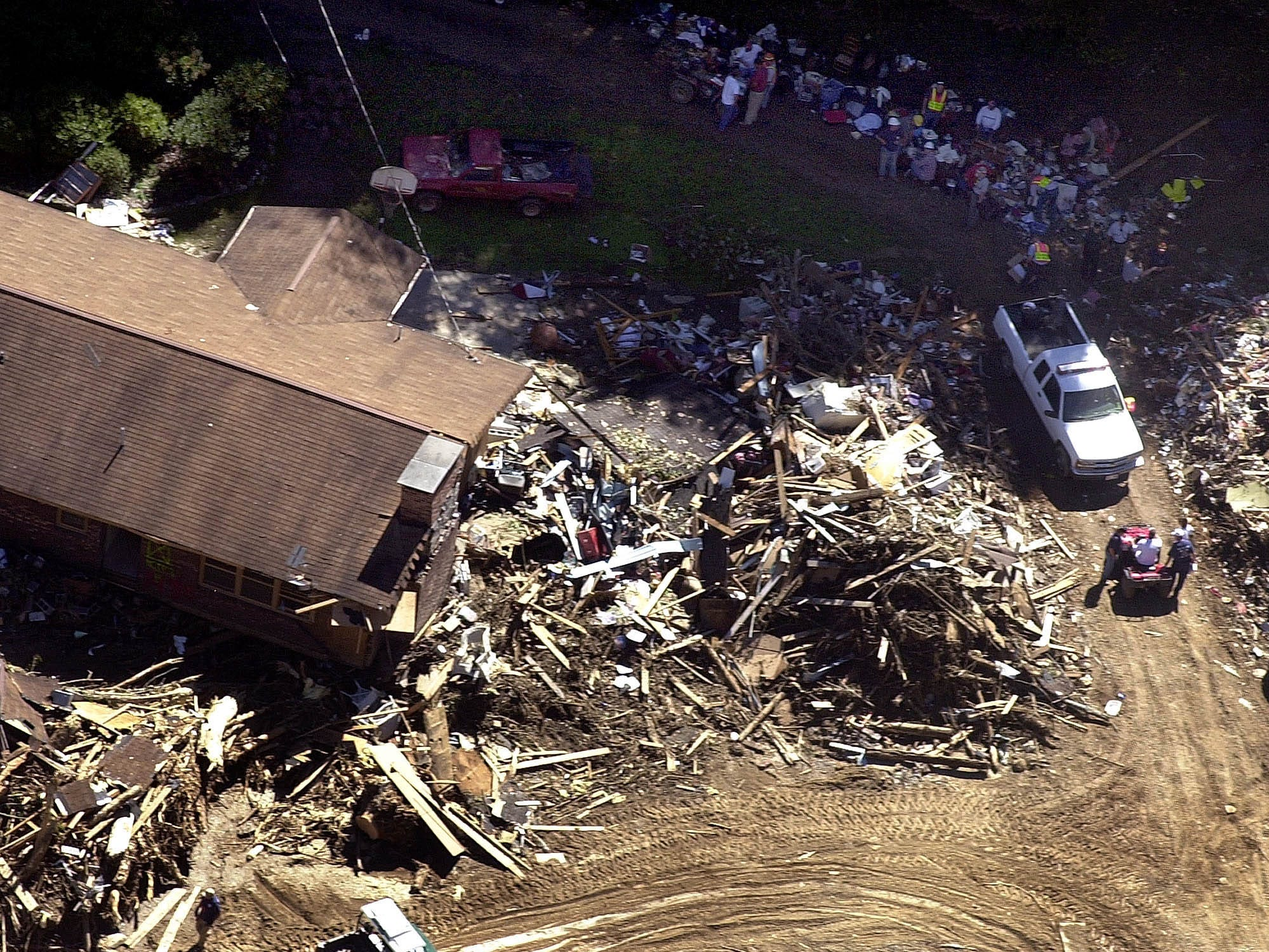 Debris surrounds a destroyed house in the Peeks Creek community, near Franklin on Sept. 20, 2004. Heavy rains from the remnants of Hurricane Ivan along with a massive rockslide claimed at least three lives last Friday. Cadaver dogs joined workers with heavy equipment Monday in the search for four people still missing after the remnants of Hurricane Ivan sent a torrent of mud, water and debris through the mountain town.