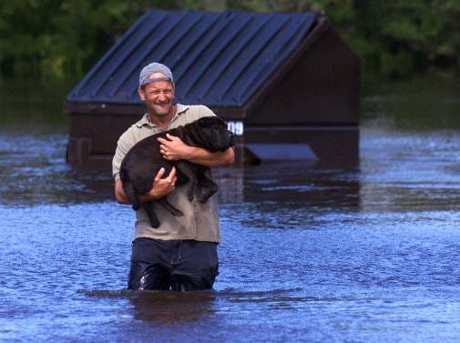 Tommy Sullivan carries his dog Isabella from the flooded parking lot of his apartment complex near Leland, N.C., Thursday, Sept. 16, 1999, after Hurricane Floyd hit the area overnight.