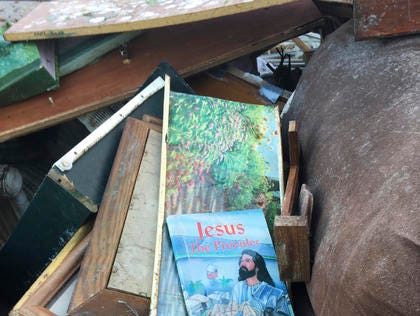 In this Dec. 1, 2016, photo, damaged photos and books sit on top of furniture ruined by Hurricane Matthew and pulled from the home of Dianne Hines in Princeville, N.C. Hines' home was rebuilt after Hurricane Floyd in 1999. This time, she says she's ready to move elsewhere.