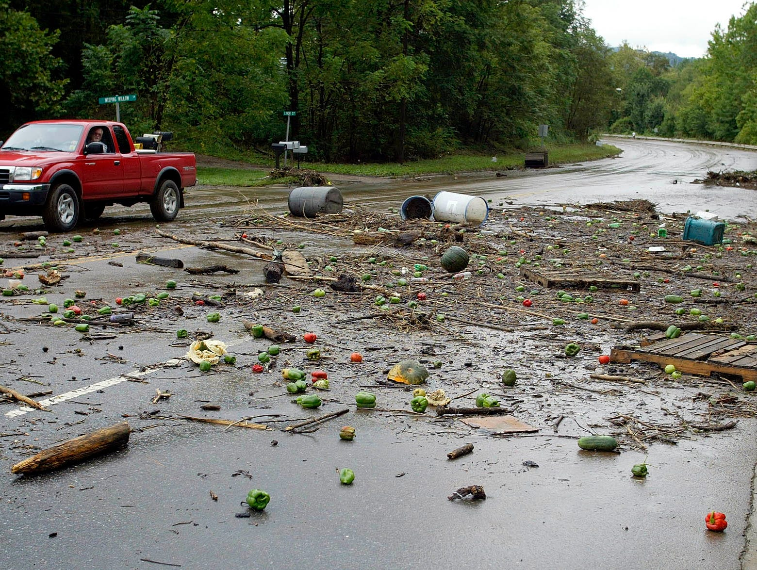 A truck drives through debris left by floodwaters in Canton on Sept. 8, 2004. Remnants of Hurricane Frances have brought heavy rains and flooding to the area.