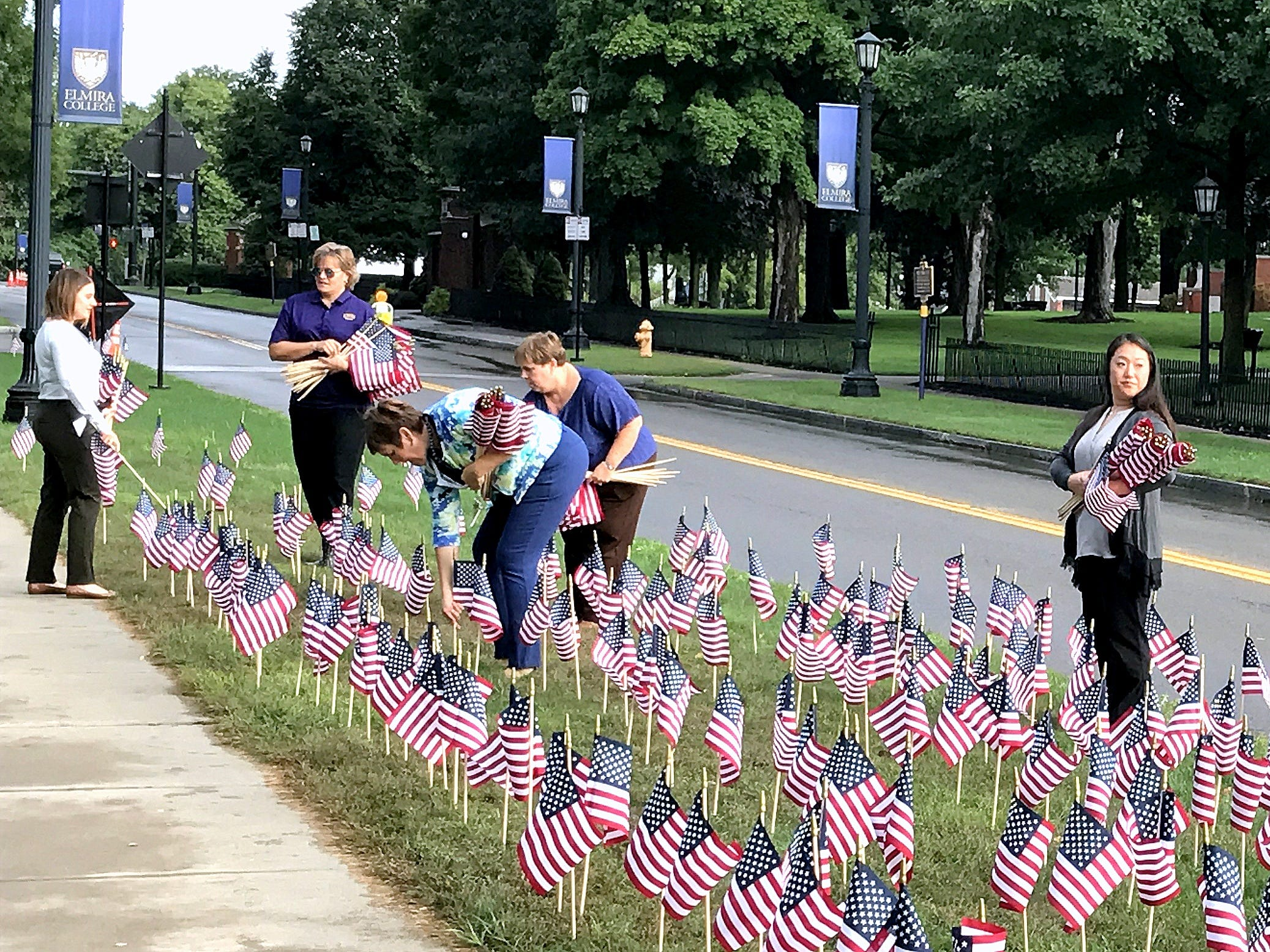 Students and faculty members of Elmira College plant nearly 3,000 American flags along Park Place in Elmira on Tuesday to honor the victims of the Sept. 11, 2001 terrorist attacks.