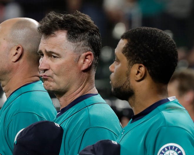 Mariners manager Scott Servais, center, and infielder Robinson Cano will miss the playoffs, barring a miracle.