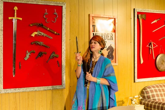 Helga (Carolyn Ripper) checks out Sydney's collection of theatrical murder weapons.