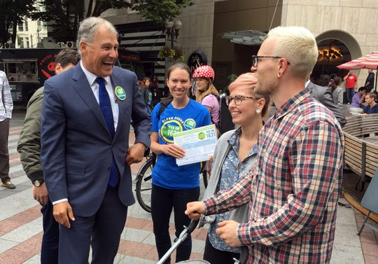Washington Gov. Jay Inslee helps gather signatures for a proposed initiative that would charge large industrial emitters a fee for their carbon emissions. Voters in Washington state will be asked this fall to do what state and federal leaders have been reluctant to: charge a direct fee on carbon pollution to fight climate change.