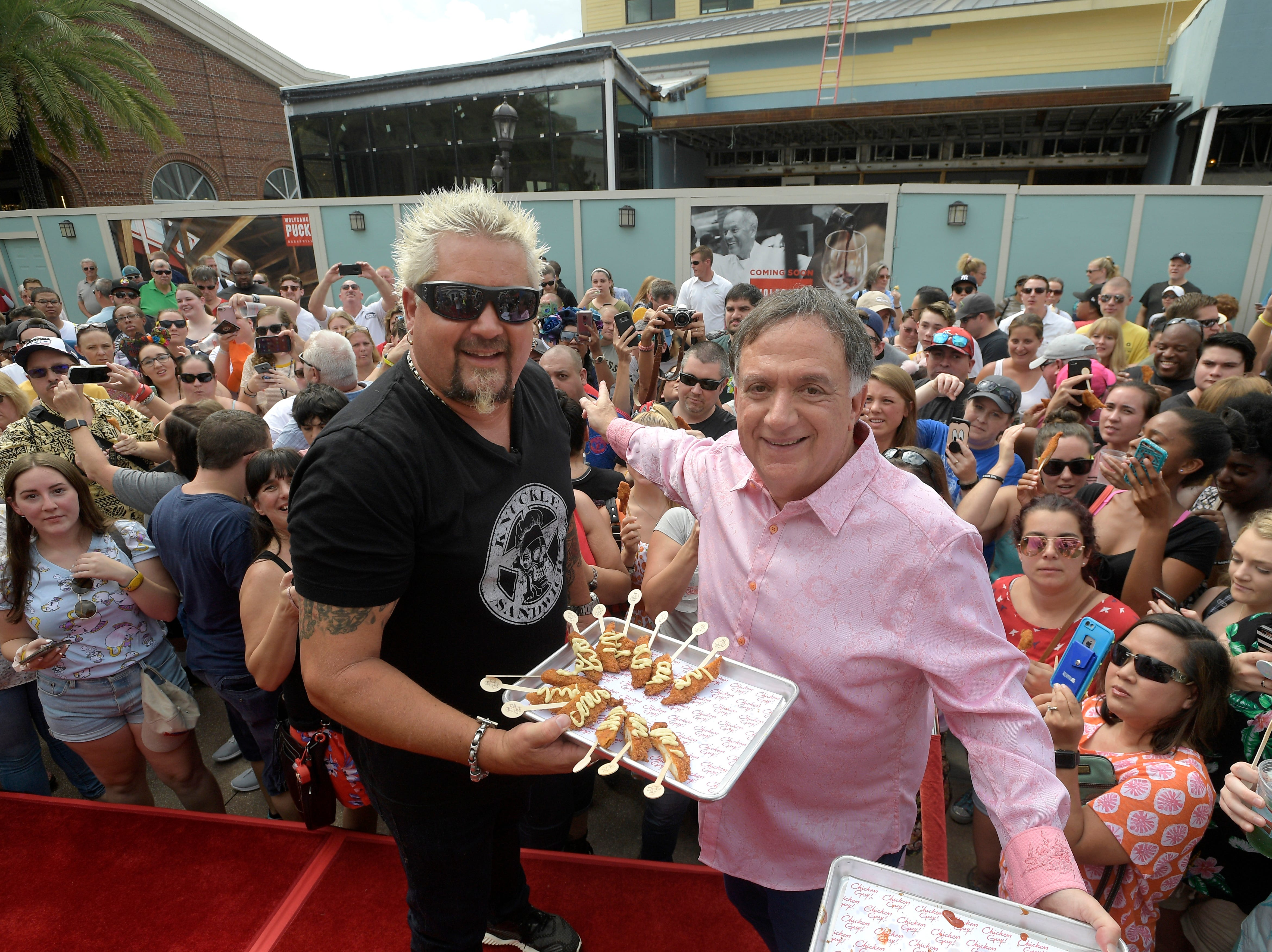 Chef Guy Fieri, left, and restaurateur, Robert Earl hand out samples to guests at Chicken Guy! at Disney Springs Monday after a special ribbon-cutting ceremony.