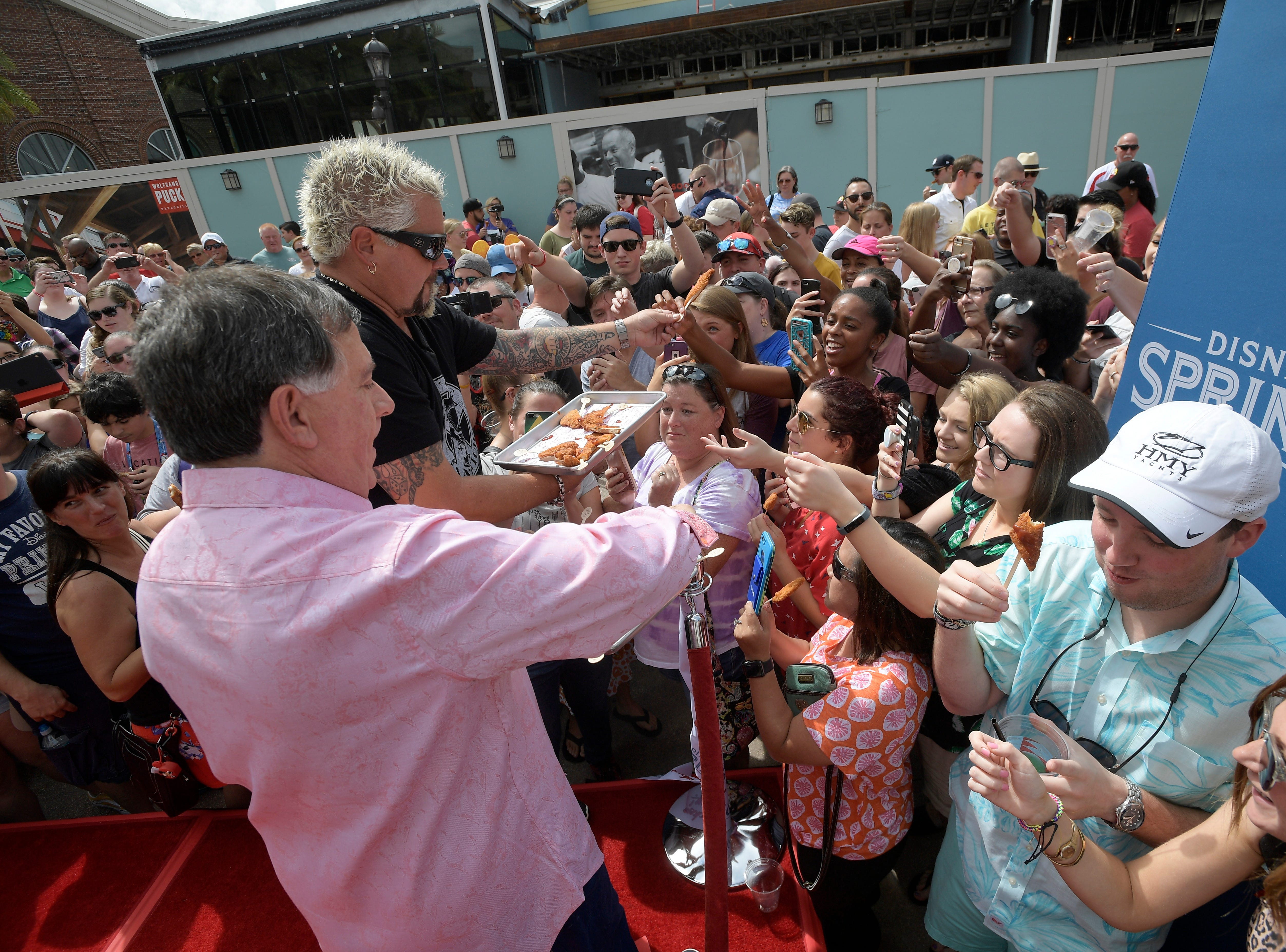 Chef Guy Fieri, and restaurateur, Robert Earl hand out samples to guests at Chicken Guy! at Disney Springs Monday after a special ribbon-cutting ceremony.
