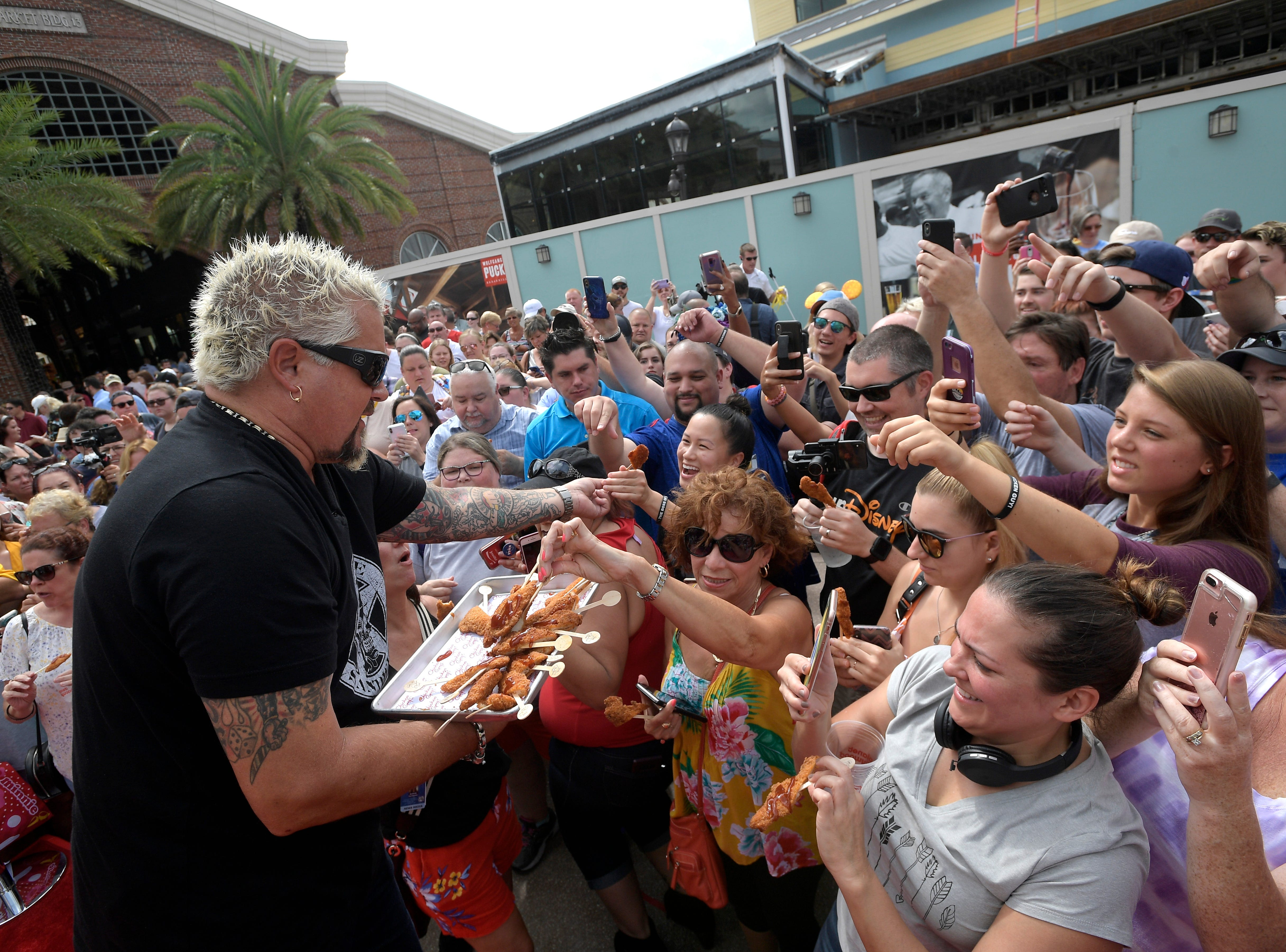 Chef Guy Fieri hands out samples to guests at Chicken Guy! at Disney Springs Monday after a special ribbon-cutting ceremony.