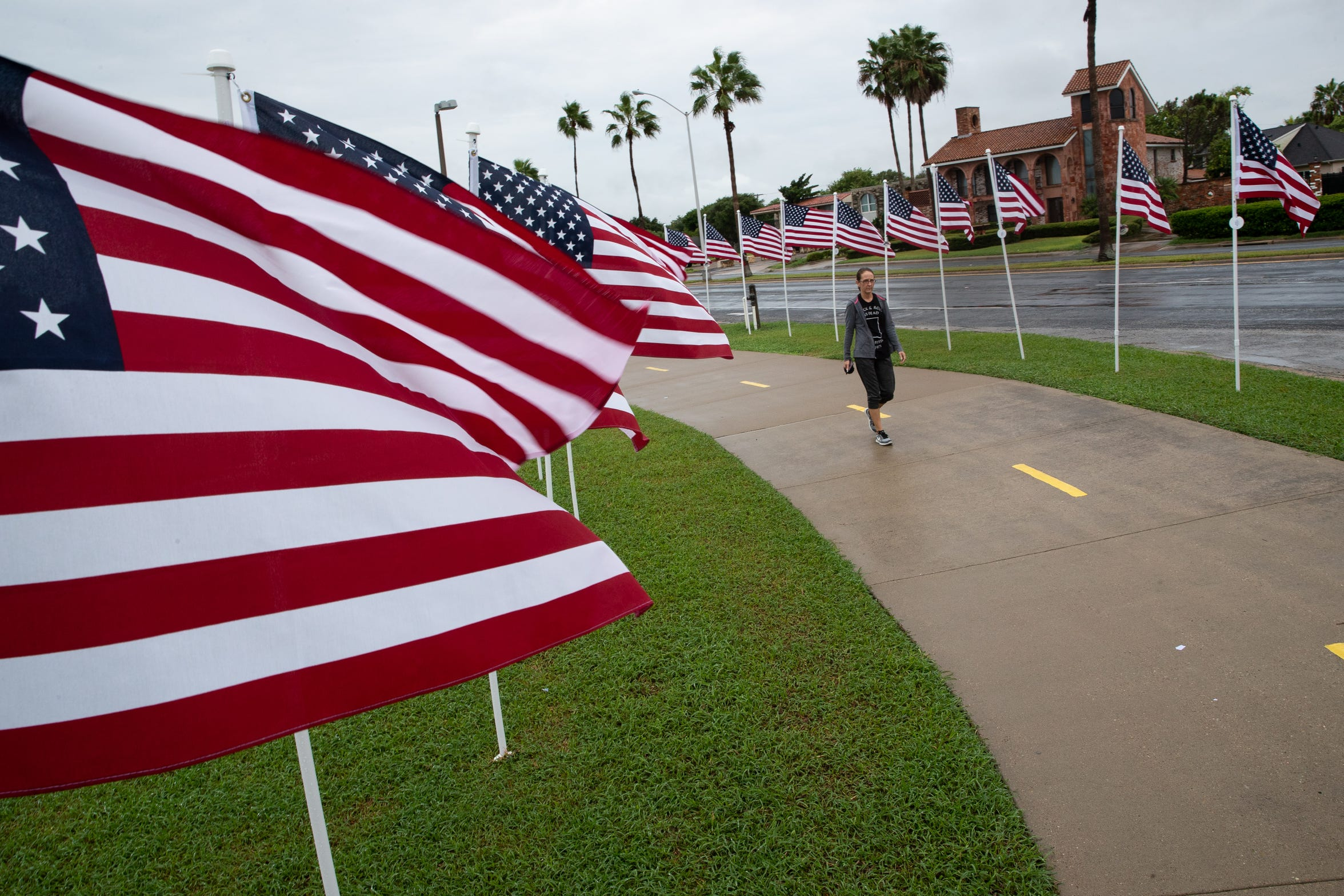 A women walks down Ocean Boulevard thought the Flags for Heroes honoring these who died in 9/11 on the 17th anniversary of the terrorist attacks on Tuesday, Sept. 11, 2018.