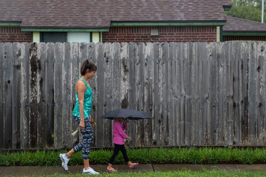 A young girl holding an umbrella and women walk down Canadian Drive as rain starts to fall Tuesday, Sept 11, 2018. The forecast calls for more rain this week in the Corpus Christi area.