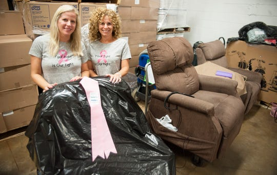 Danielle Stuffo, right, and Danielle Koenig, both of Mount Laurel, who began offering chairs of comfort to women who are battling breast cancer, stand in the donated warehouse space in Moorestown where they store the chairs.