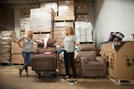 "Danielle Stuffo, right, and Danielle Koenig, both of Mount Laurel, who began offering chairs of comfort to women who are battling breast cancer, stand in the donated warehouse space in Moorestown where they store the chairs. Their nonprofit is called ""The Recovery Chair."""