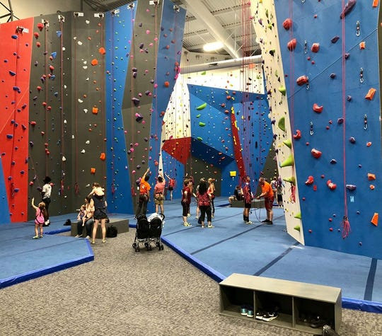 Instructors encourage climbing novices to take it one step at a time on 40-foot-plus climbing walls.