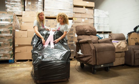 Danielle Stuffo, right, and Danielle Koenig, both of Mount Laurel, place a ribbon on a chair that will soon be delivered as they stand in the donated warehouse space in Moorestown where they store the chairs. The duo began offering chairs of comfort to women who are battling breast cancer.