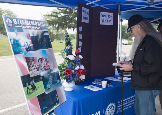 """Army veteran and former Chillicothe teacher Joe Helsel writes down his memories of 9/11 for the """"Where Were You"""" board after the VA's 9/11 Remembrance Ceremony Tuesday morning."""