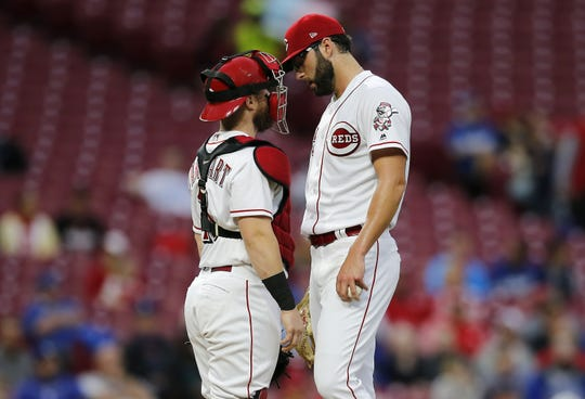 Cincinnati Reds catcher Tucker Barnhart (16) visits starting pitcher Cody Reed (25) at the mound in the top of the first inning of the MLB National League game between the Cincinnati Reds and the Los Angeles Dodgers at Great American Ball Park in downtown Cincinnati on Monday, Sept. 10, 2018.