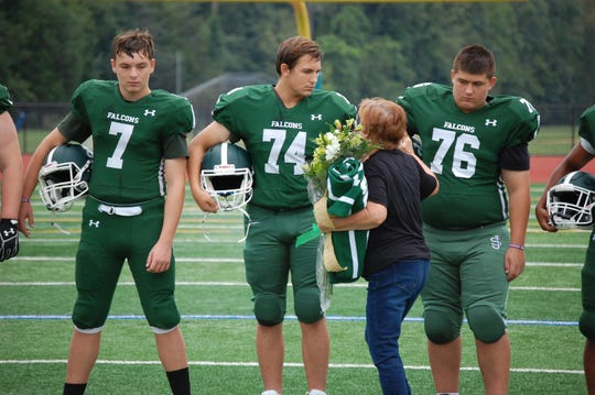 Patricia Cleary, wife of beloved former St. Joseph assistant coach Michael Cleary, greets players during Saturday's pregame ceremony.