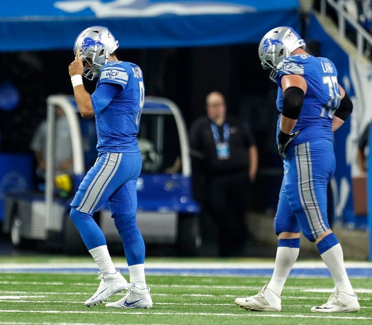 Detroit Lions quarterback Matthew Stafford (9) and guard T.J. Lang (76) walk off the field after an interception by the New York Jets during the second half at Ford Field in Detroit, Monday, Sept, 10, 2018.