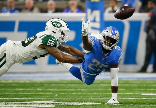 Detroit Lions running back Theo Riddick reaches for the ball as New York Jets linebacker Kevin Pierre-Louis defends in the first half in Detroit, Monday, Sept. 10, 2018.