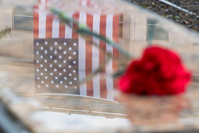 The image of the American flag is seen reflected in water under a flower placed over the name of a fallen individual, before a remembrance ceremony at the at the National 9/11 Pentagon Memorial in Arlington, Virginia on September 11, 2018.