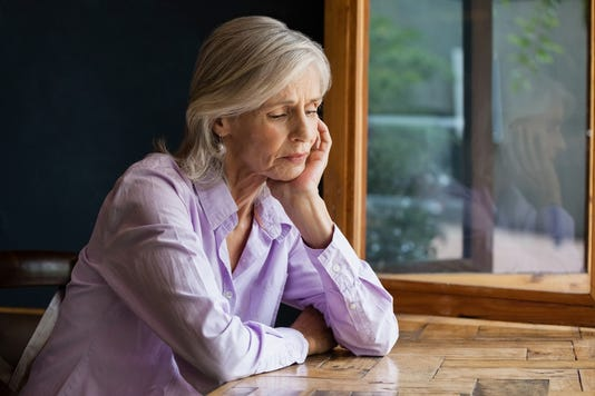 Sad Senior Woman Sitting At Table