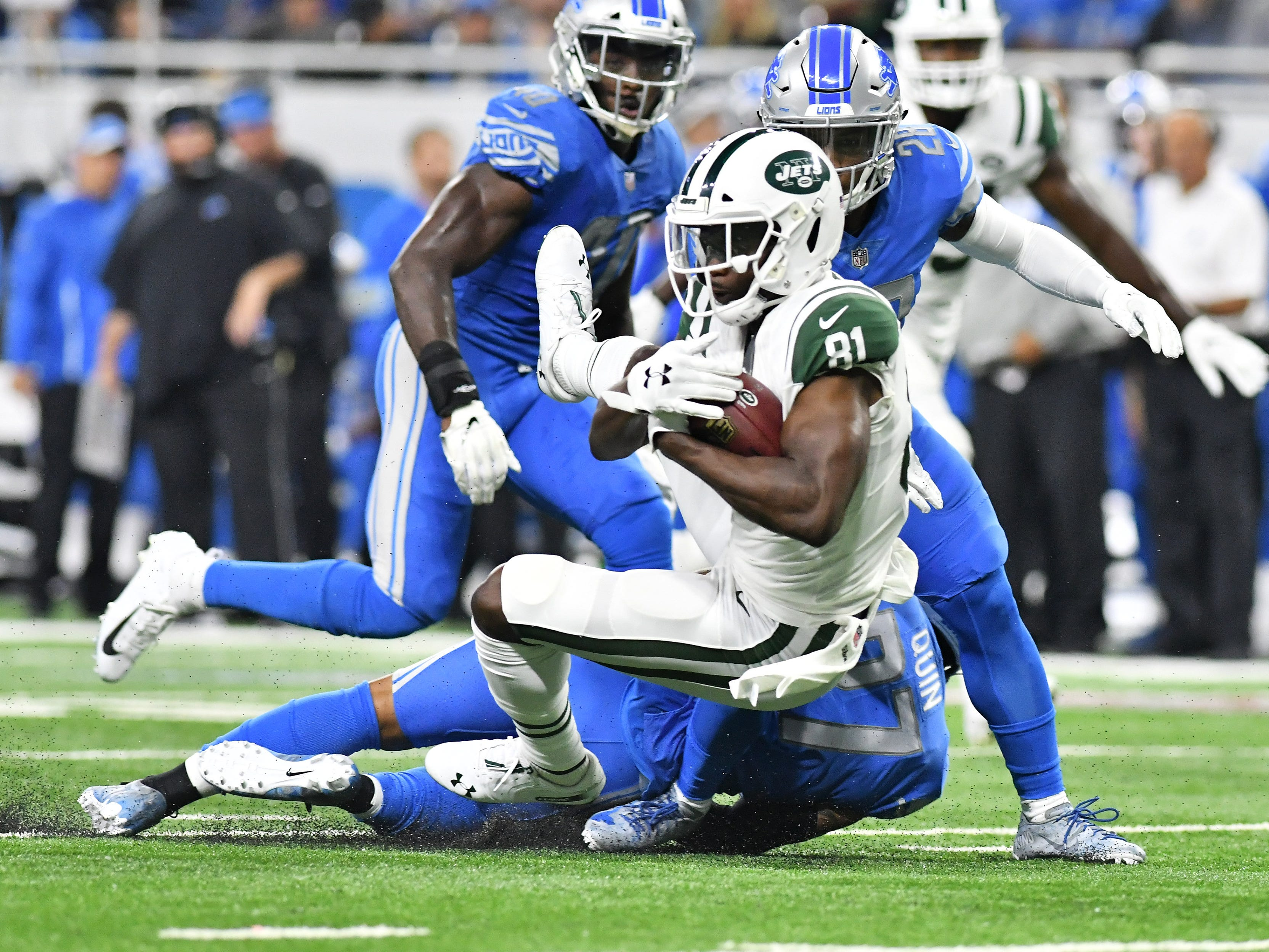 Lions Glover Quin, bottom, and Quandre Diggs converge on Jets' Quincy Enunwa (81) in the first quarter.
