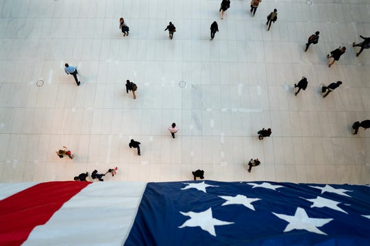 People walk under an American flag inside the Oculus, part of the World Trade Center transportation hub, on the anniversary of 9/11 terrorist attacks in New York on Tuesday, Sept. 11, 2018.