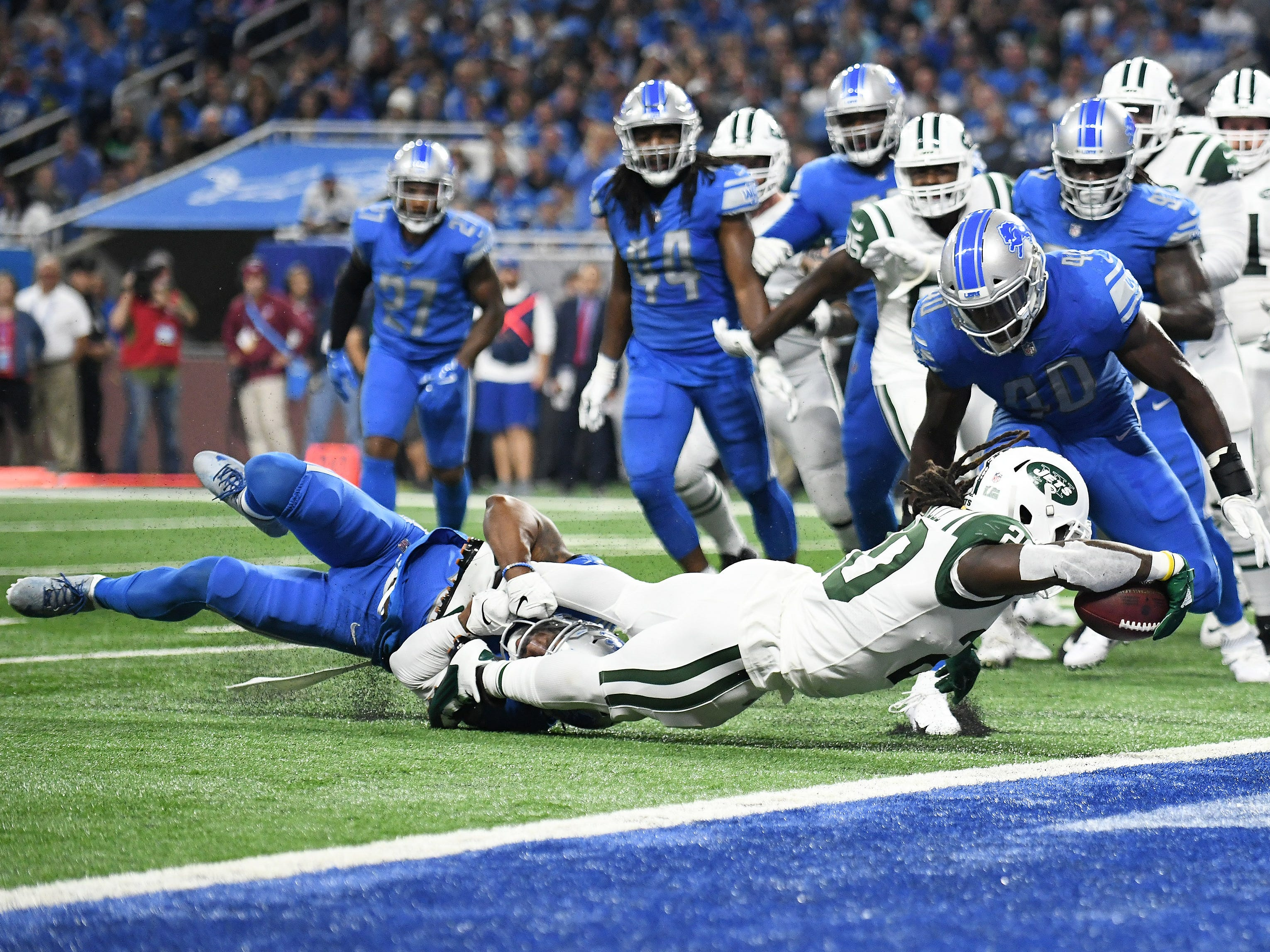 Lions' Quandre Diggs tries to tackle Jets running back Isaiah Crowell but Crowell scores a touchdown in the first half.