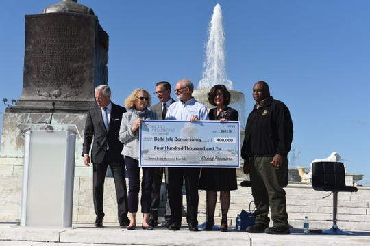 Bud Denker (from left), Chevrolet Detroit Grand Prix, Sarah Earley, Belle Isle Conservancy, Michael Simcoe, vice-president of Global Design for GM, Robert Carpenter, DTE Energy, Michele Hodges, president, Belle Isle Conservancy, and Karis Floyd, Michigan Department of Natural Resources pose with a symbolic giant check at The Scott Fountain on Belle Isle on Tuesday, September 11, 2018, representing a contribution of $400,000 from the 2018 Grand Prixmiere fundraiser to help keep the fountain working.