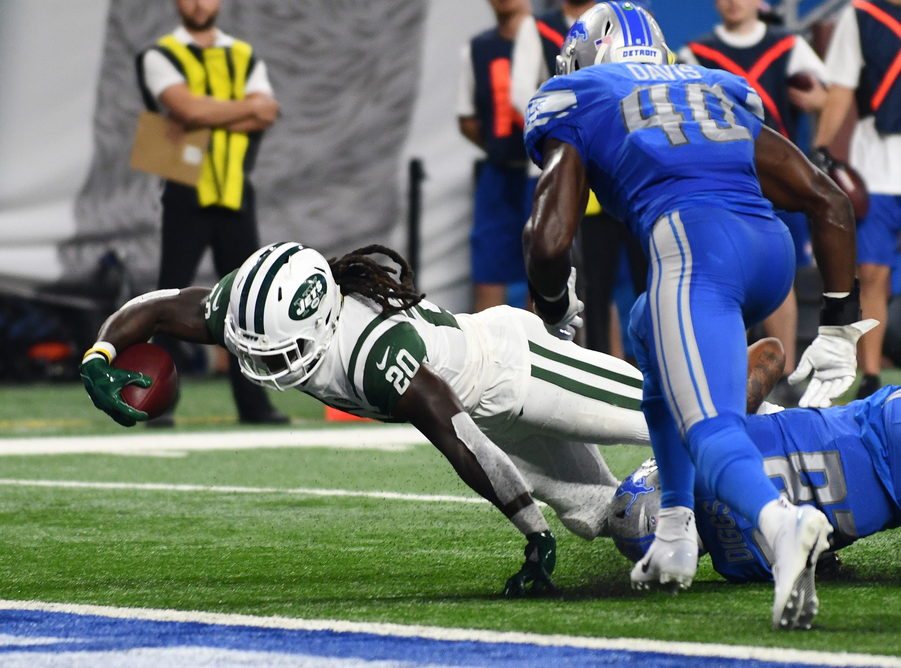 Jets' Isaiah Crowell reaches for the end zone and scores past Lions Quandre Diggs and Jarrad Davis in the first quarter.