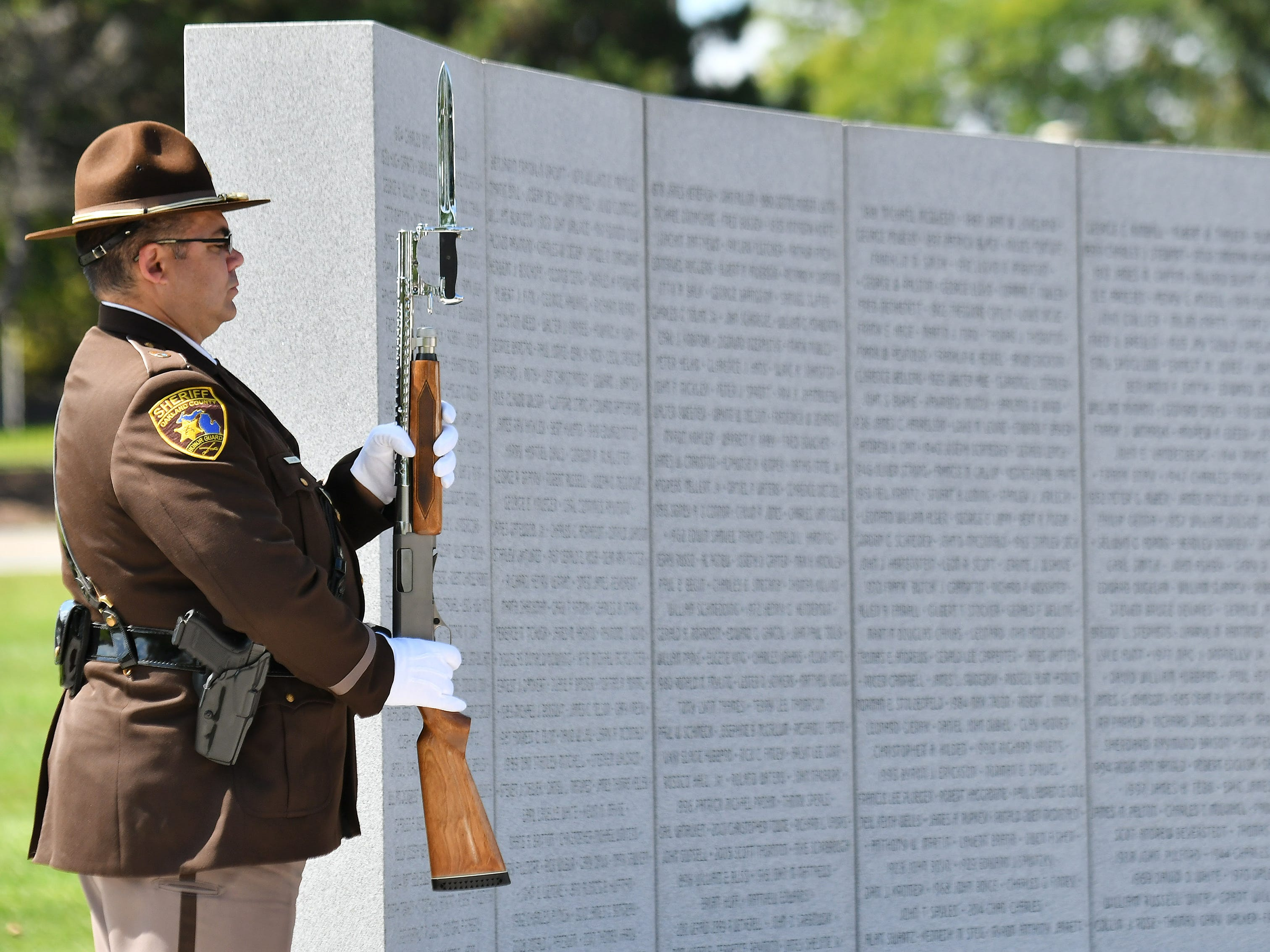 An Oakland County Sheriff deputy stands at attention near the wall with the names of the fallen during the ceremony.