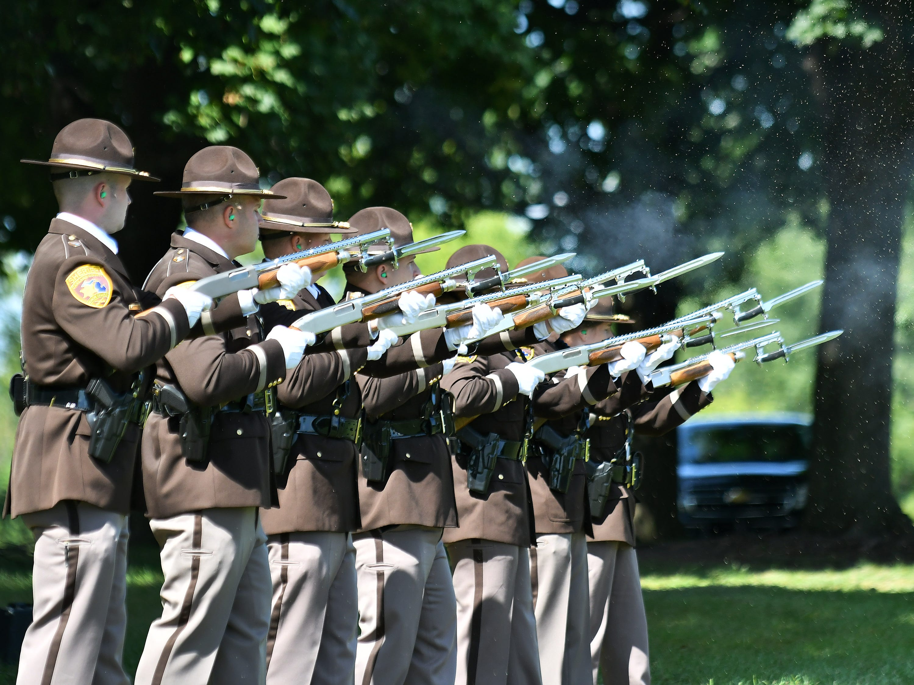The Oakland County Sheriff's Office Honor Guard performs a 21-gun salute.
