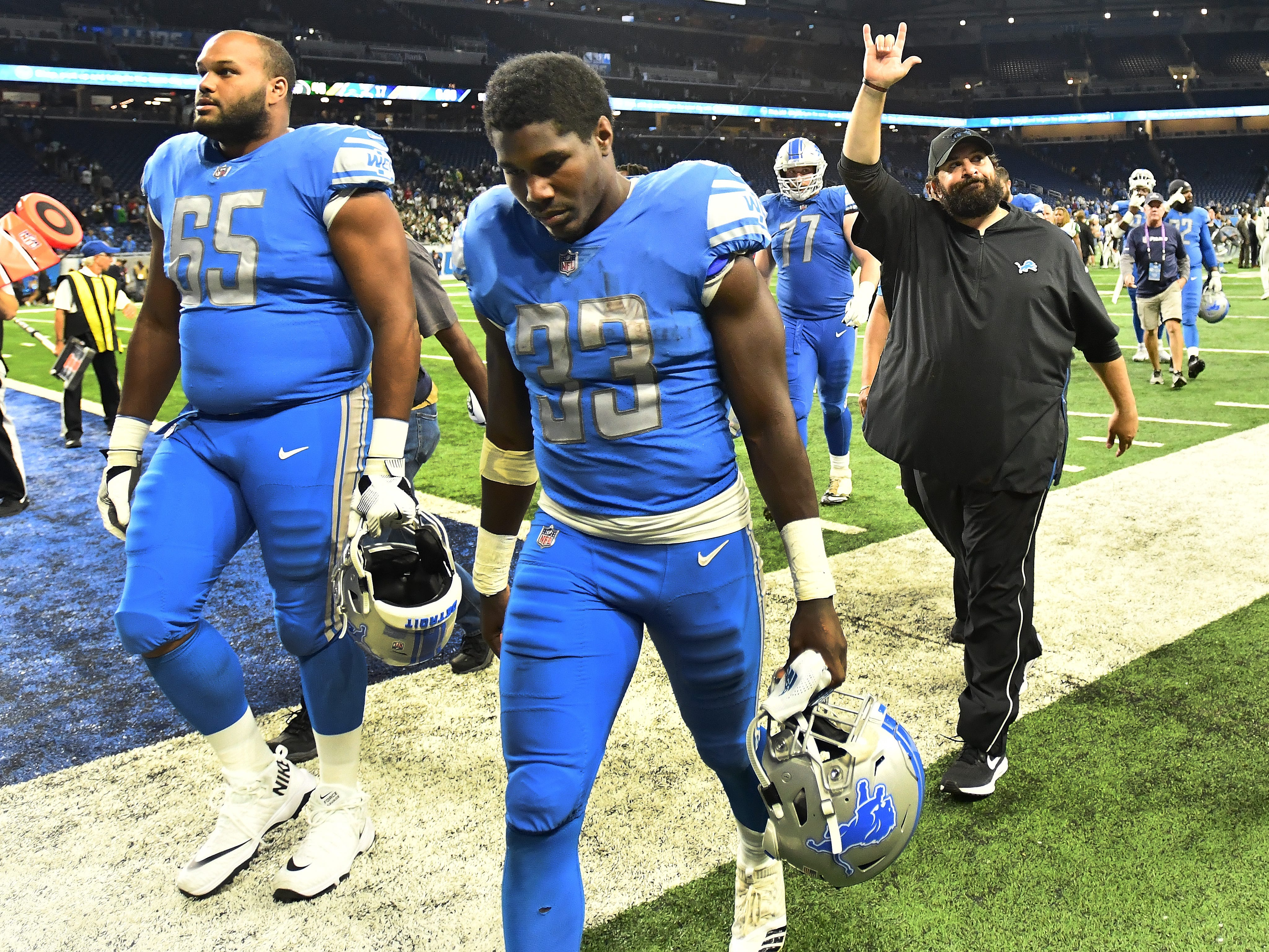 Lions rookies Tyrell Crosby and Kerryon Johnson leave the field with head coach Matt Patricia gesturing toward the stands after the 48-17 loss to the New York Jets.