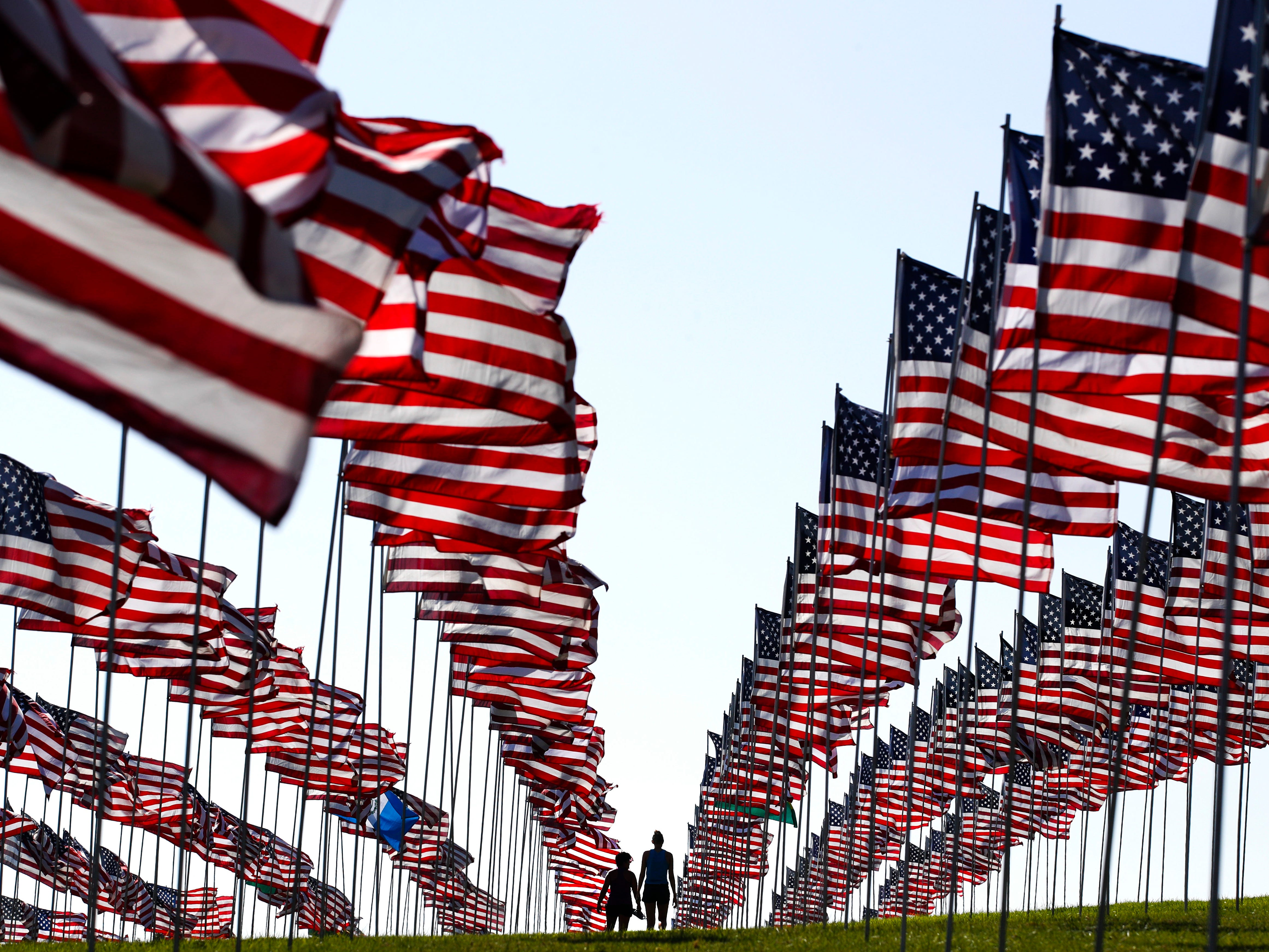 Bianca Burton, center left, and Erin Schultheis walk around the Pepperdine University's annual display of flags honoring the victims of the 9/11 terrorist attacks, Monday, Sept. 10, 2018, in Malibu, Calif. Terrorists used hijacked planes to crash Sept. 11, 2001, into the World Trade Centers, the Pentagon and a field in Pennsylvania. Nearly 3,000 people were killed in the attacks.
