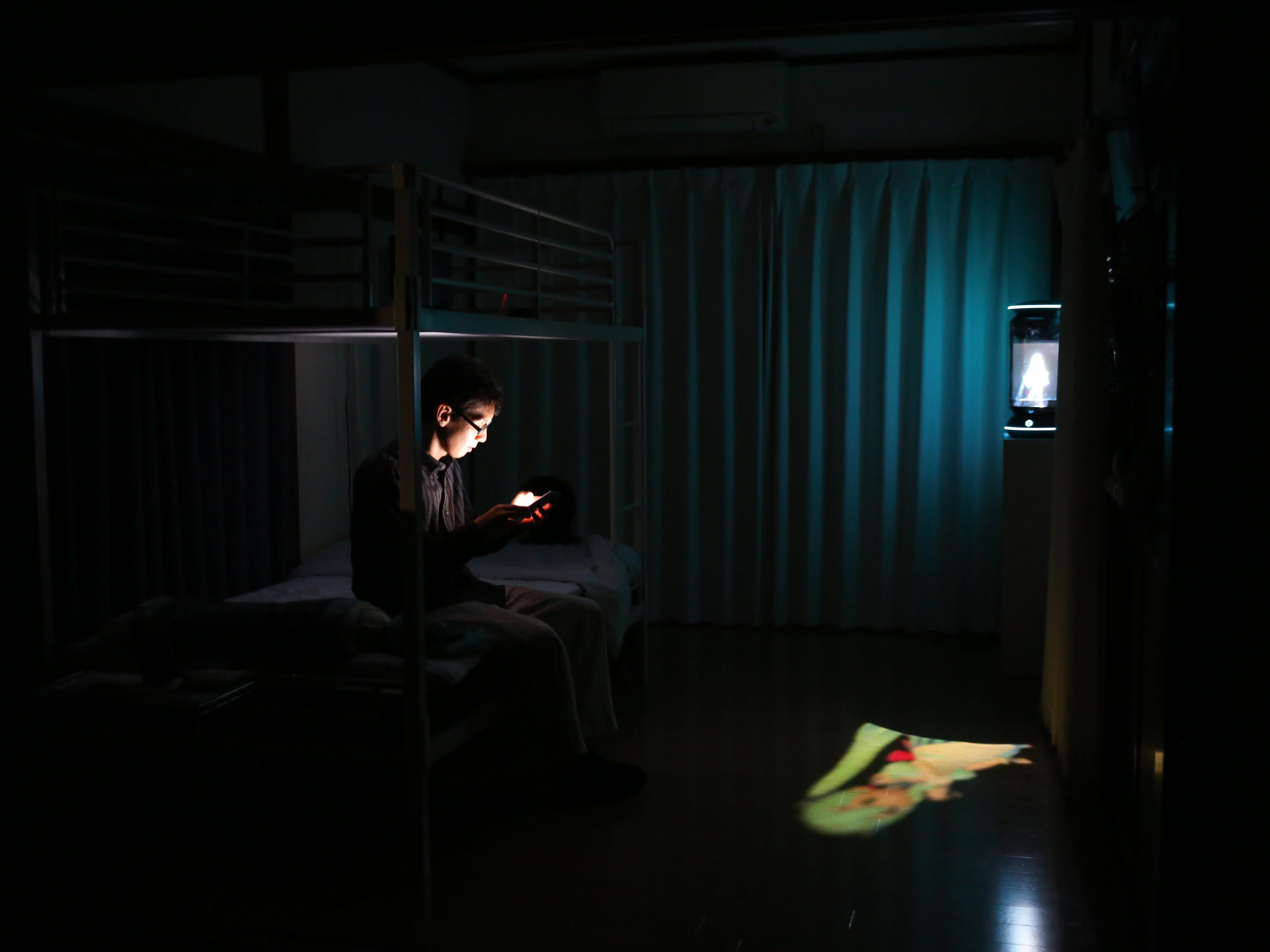 Akihiko Kondo uses his phone with 'Hatsune Miku' in the background before going to bed at his house on September 11, 2018 in Tokyo, Japan. Akihiko Kondo, a 35 year-old school clerk living in Tokyo, has recently announced on twitter his plans to marry 'Hatsune Miku', the two dimensional virtual idol, on 4th of November, 2018, after having been in love with her for 10 years. Every day he plays with the 'Gatebox', a home AI communication device designed to let the users live with their favourite virtual characters.