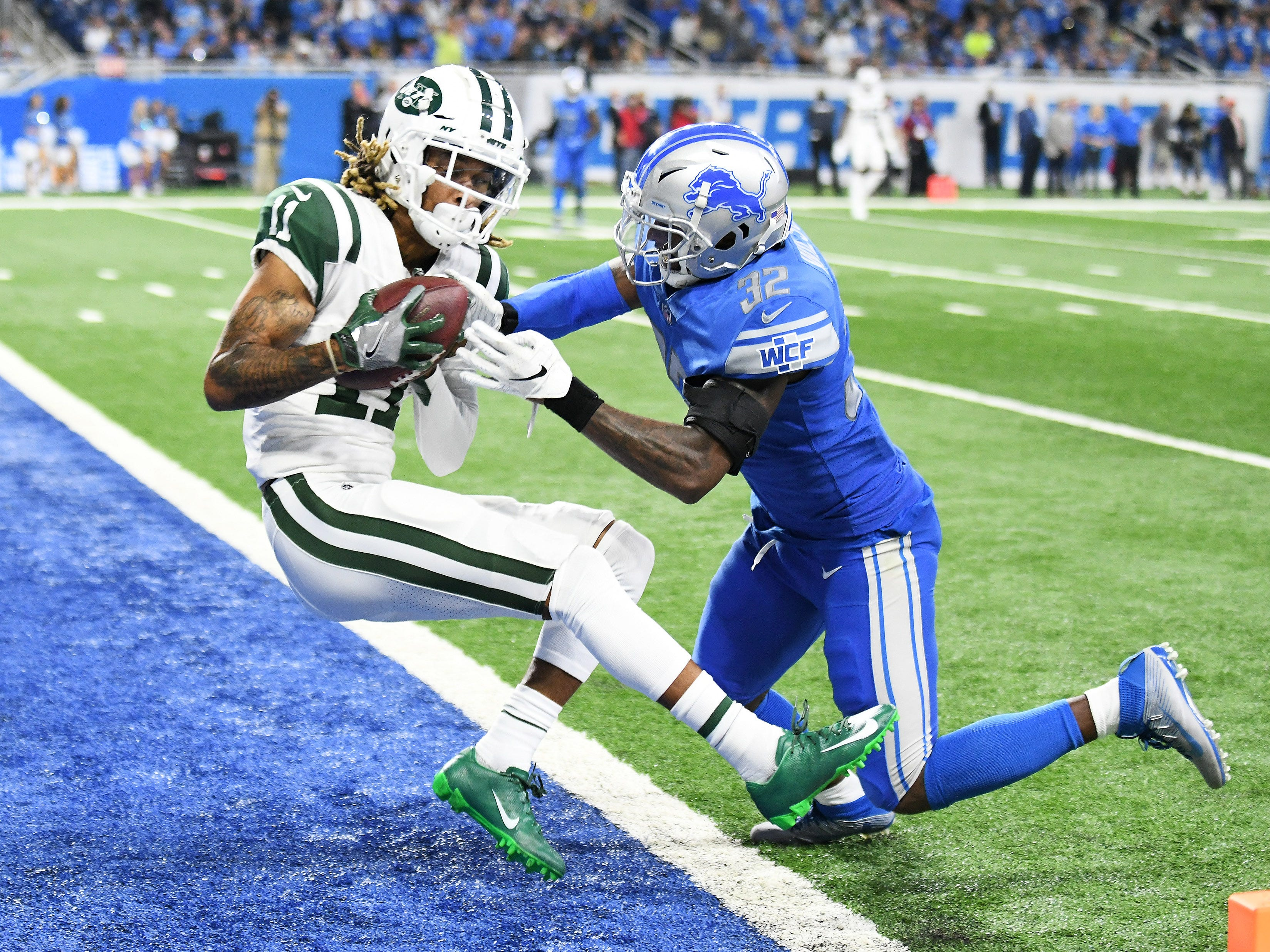 Jets' Robby Anderson (11) holds on to the ball to score a touchdown despite the efforts of Lions defensive back Tavon Wilson in the first quarter.