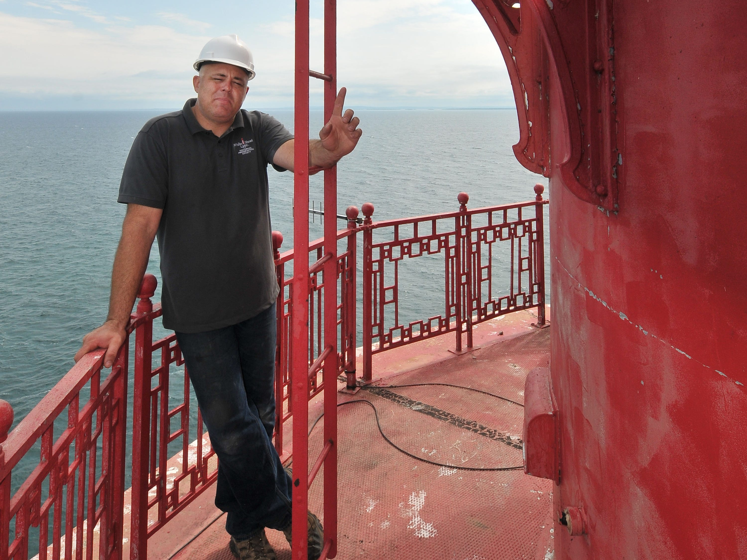 Brent Tompkins of Traverse City stands on the catwalk of the White Shoal Lighthouse, Sunday, Sept. 2, 2018 as he explains the unique aluminum trim on the light tower. The light is the only one on the Great Lakes that used aluminum, all others had cast iron.
