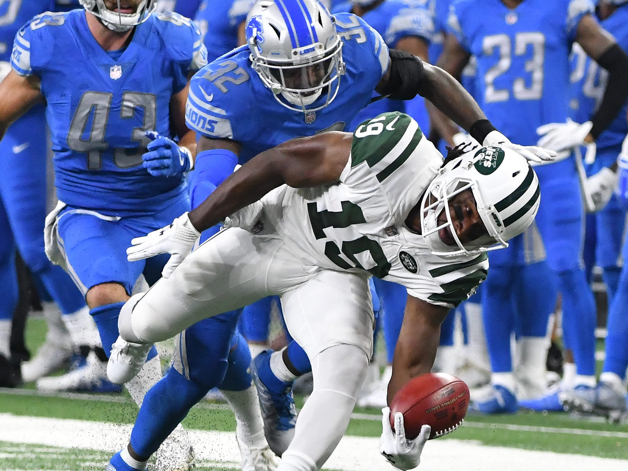 Jets' Andre Roberts is brought down by Lions' Tavon Wilson in the first quarter.