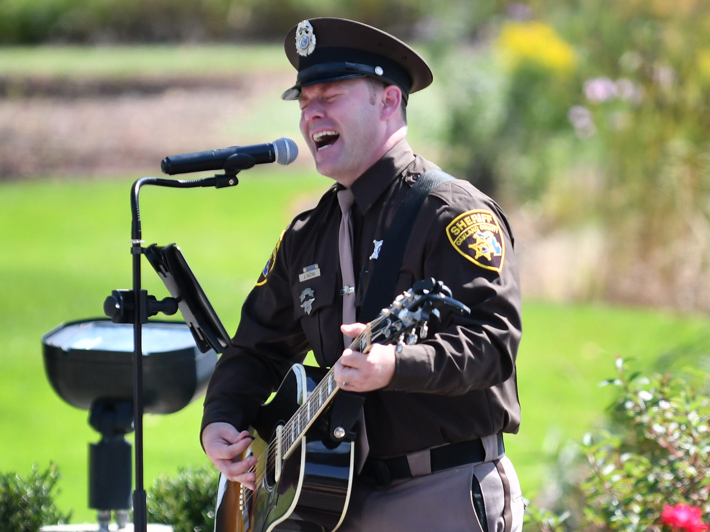 "Oakland County Sheriff Deputy Justin Rose sings a song he wrote entitled ""Hold the Line"" during the ceremony."