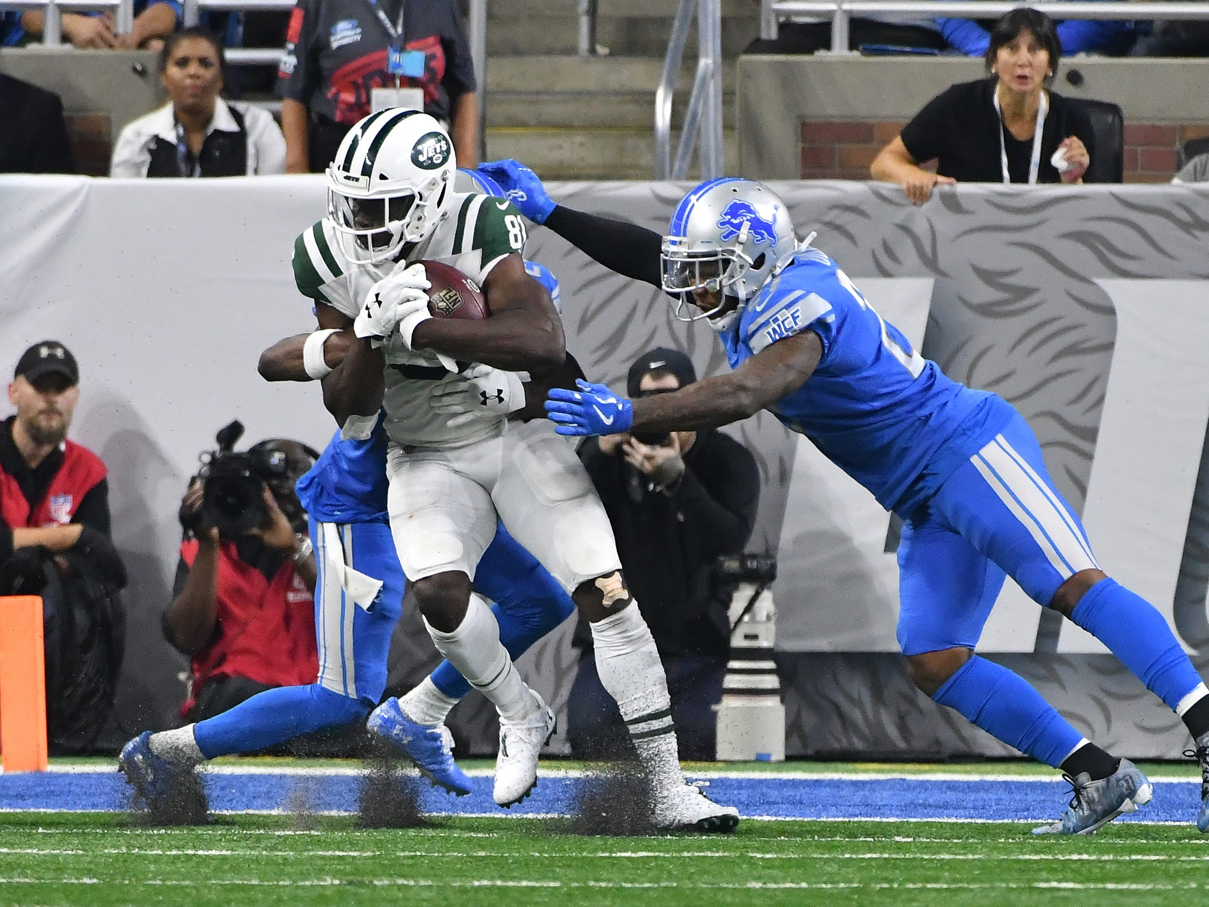 Jets' Quincy Enuwa muscles his way into the engine with Lions' Nevin Lawson and Quandre Diggs defending in the third quarter.