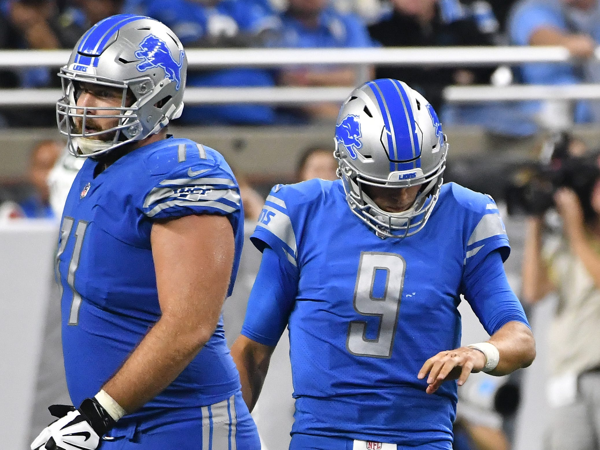 Lions' Matthew Stafford, with offensive lineman Rick Wagner, looks down at his hand after throwing an interception to Jets' Darron Lee in the third quarter.
