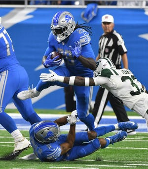 Lions running back LeGarrette Blount leaps over his teammate during a run in the second quarter.