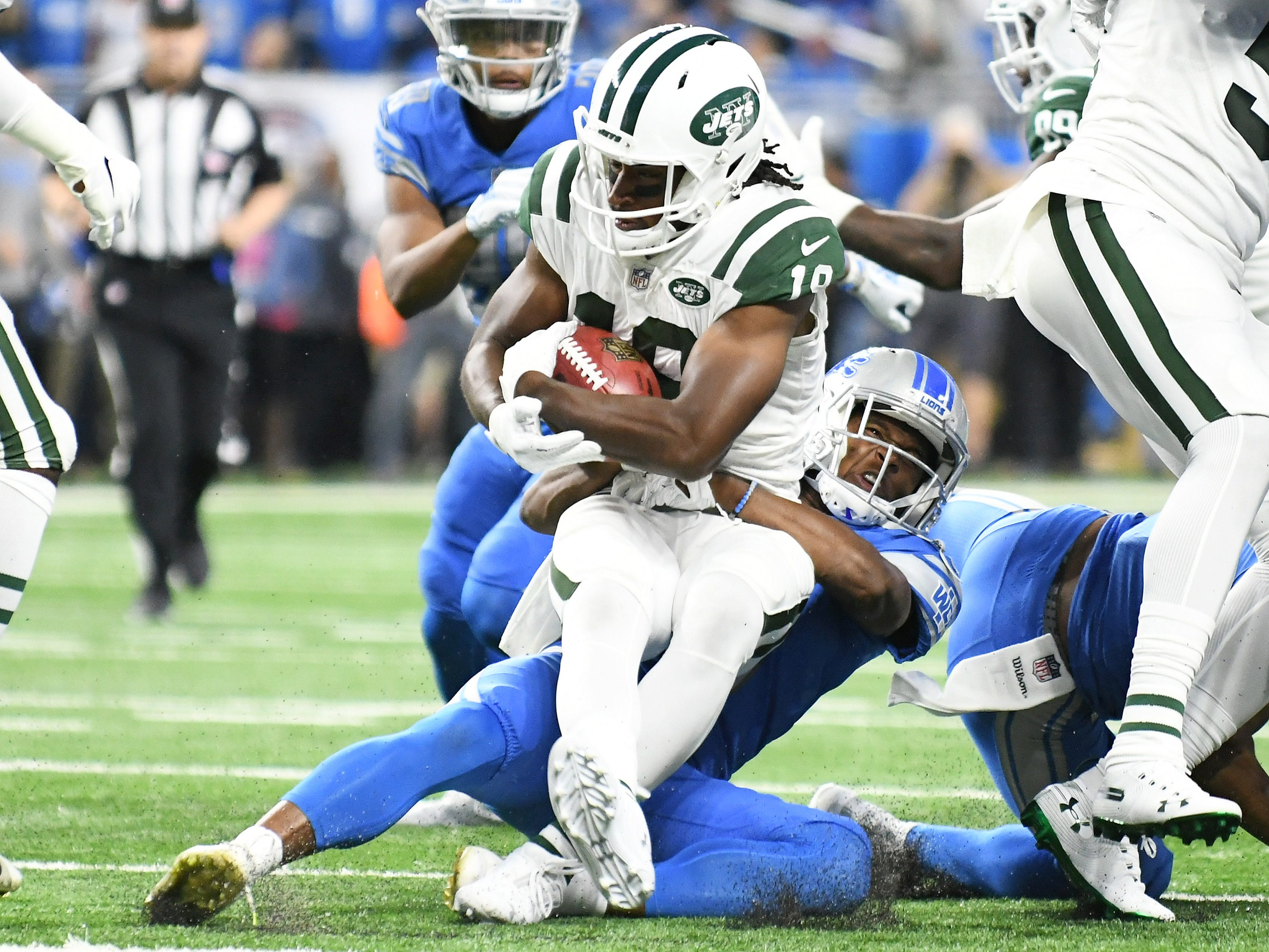 Lions safety Charles Washington ties up Jets wide receiver Andrew Roberts (19) in the first half.