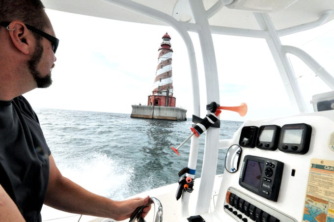 Andy Bayley of Lake Orion approaches the White Shoal Lighthouse Sunday, Sept. 2, 2018 to deliver tubing for plumbing and supplies. The 108-year-old light has new owners as of Sept of 2016, and work is slowly progressing to make the structure safe and livable.