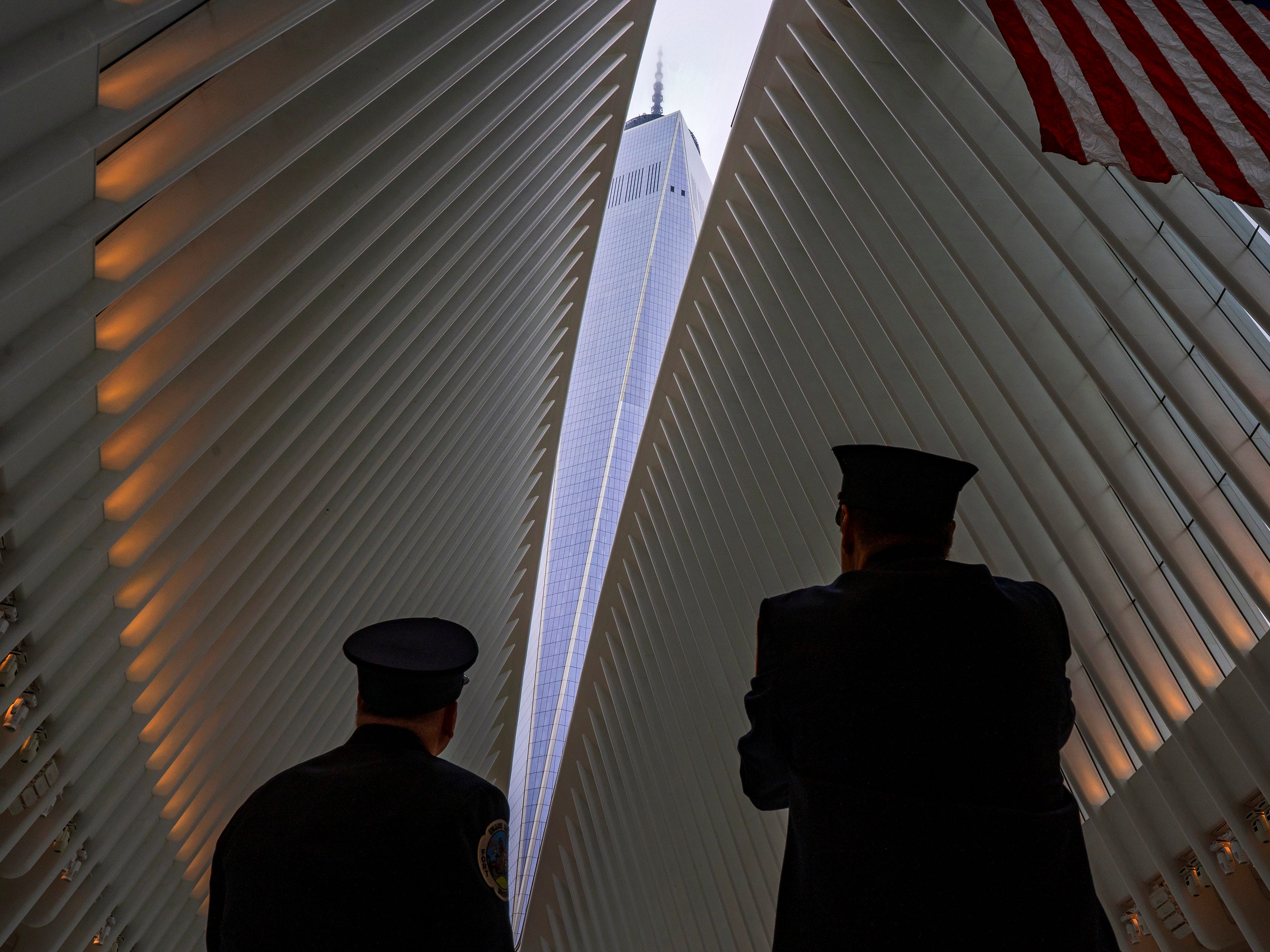 Two members of the New York City fire department look towards One World Trade Center through the open ceiling of the Oculus, part of the World Trade Center transportation hub in New York, Tuesday, Sept. 11, 2018, the anniversary of 9/11 terrorist attacks. The transit hall ceiling window was opened just before 10:28 a.m., marking the moment that the North Tower of the World Trade Center collapsed on September 11, 2001.