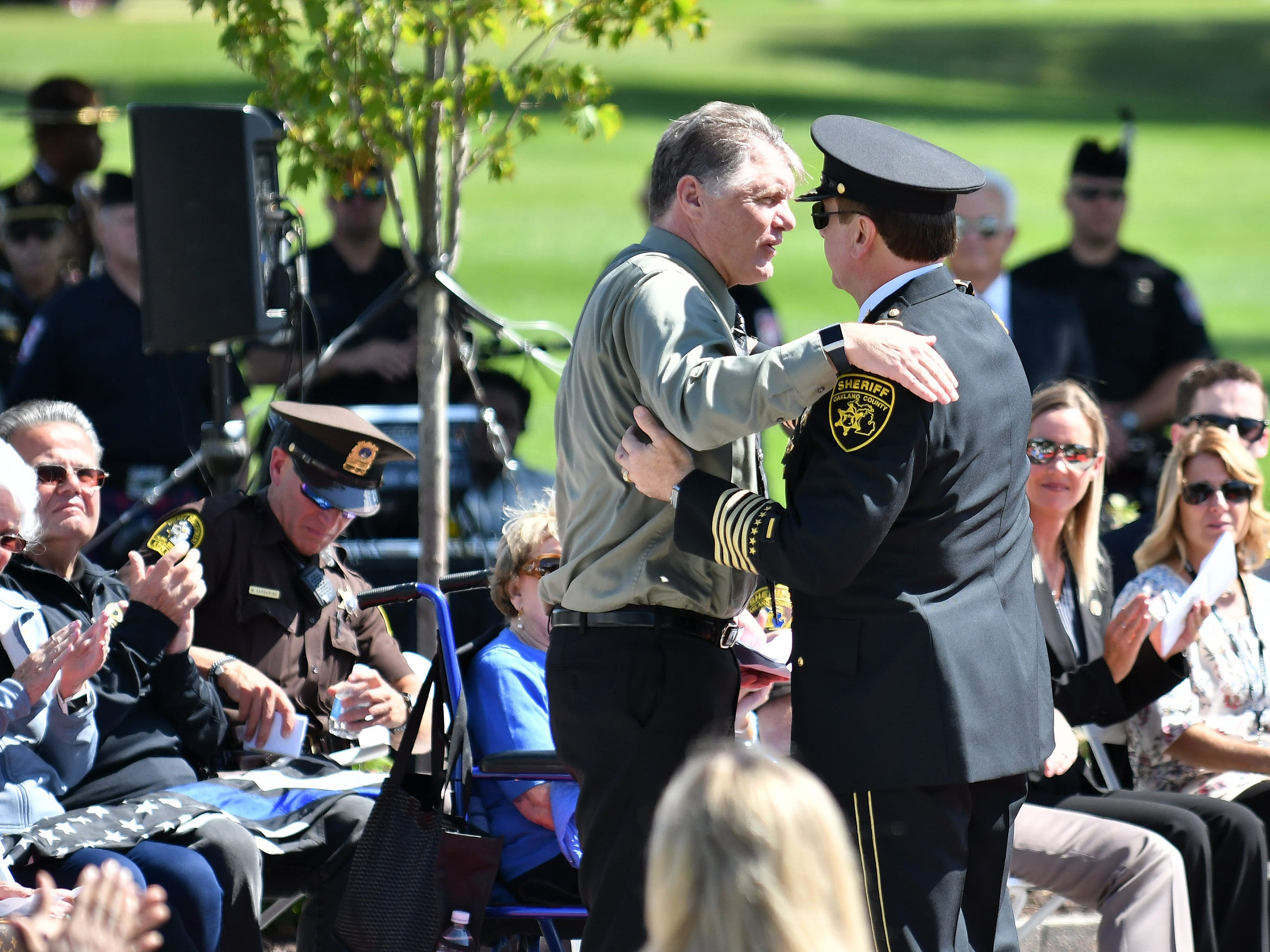 Oakland County Sheriff Michael Bouchard, right, hugs Deputy David Hack, who injured in the line of duty this year.