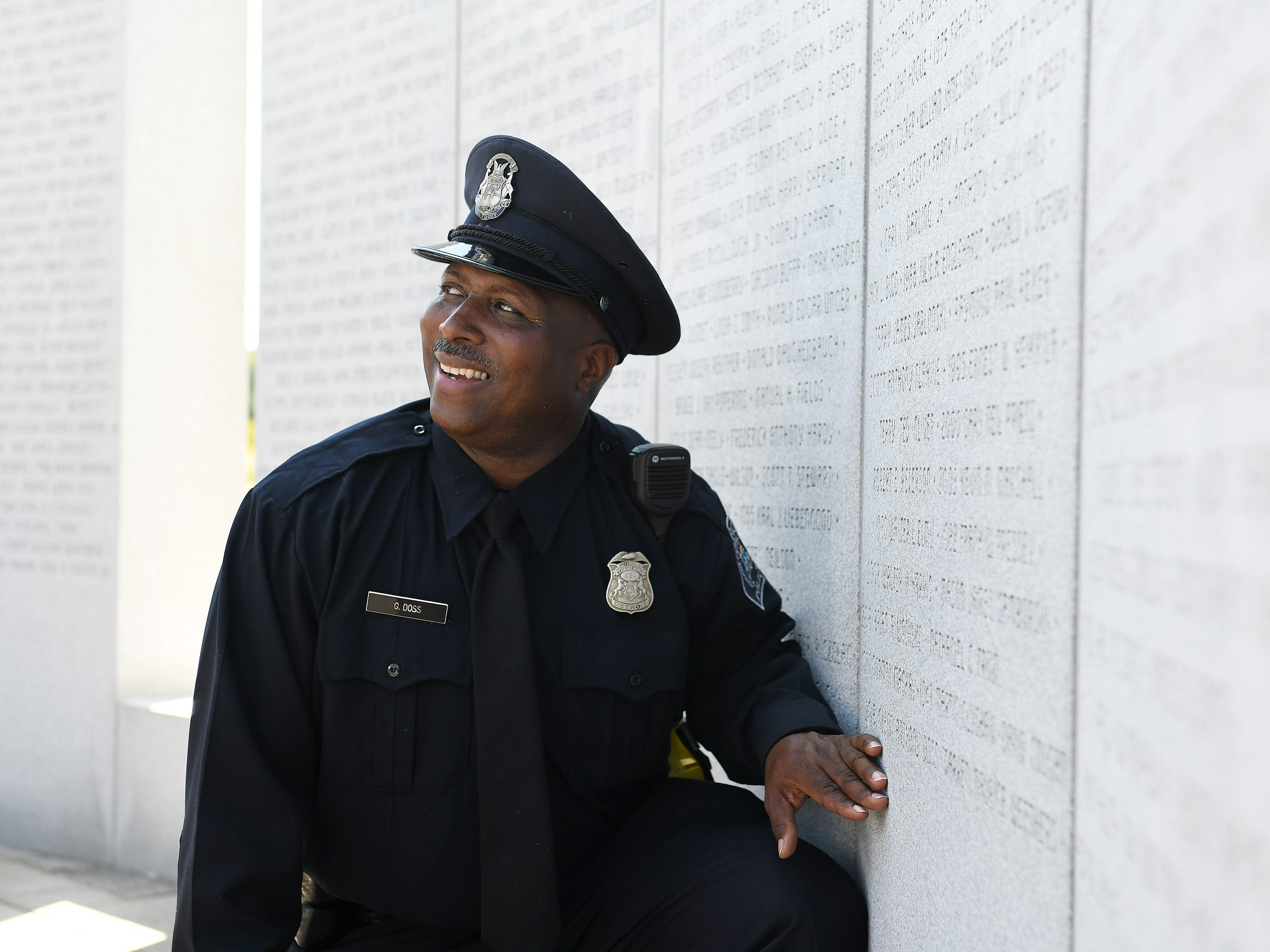 After the ceremony, Detroit police officer Glenn Doss Sr. is photographed where his son's name, officer Glenn Anthony Doss, is etched on the memorial.