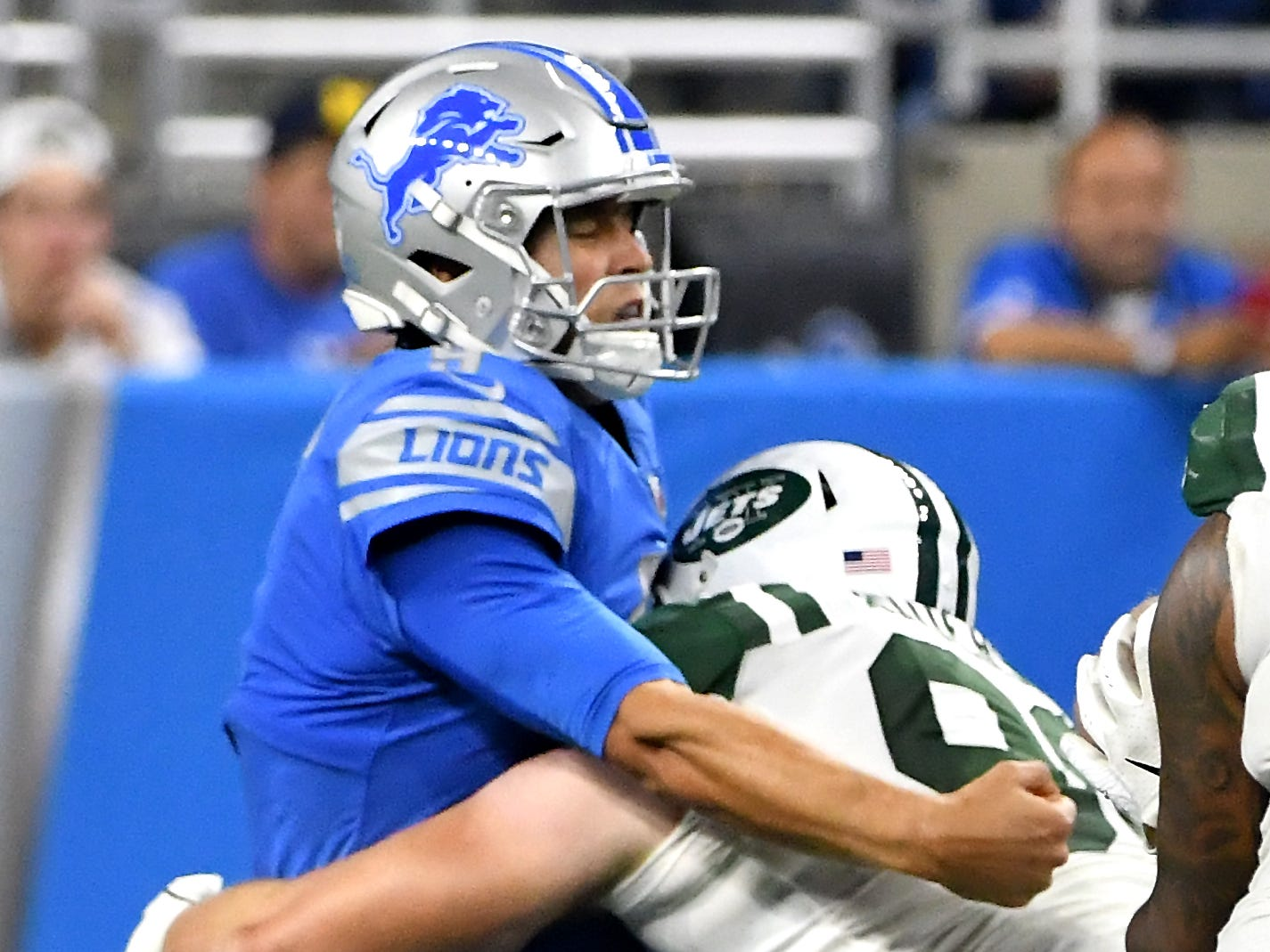 Lions' Matthew Stafford is hit by Jets' Henry Anderson after throwing in the third quarter.