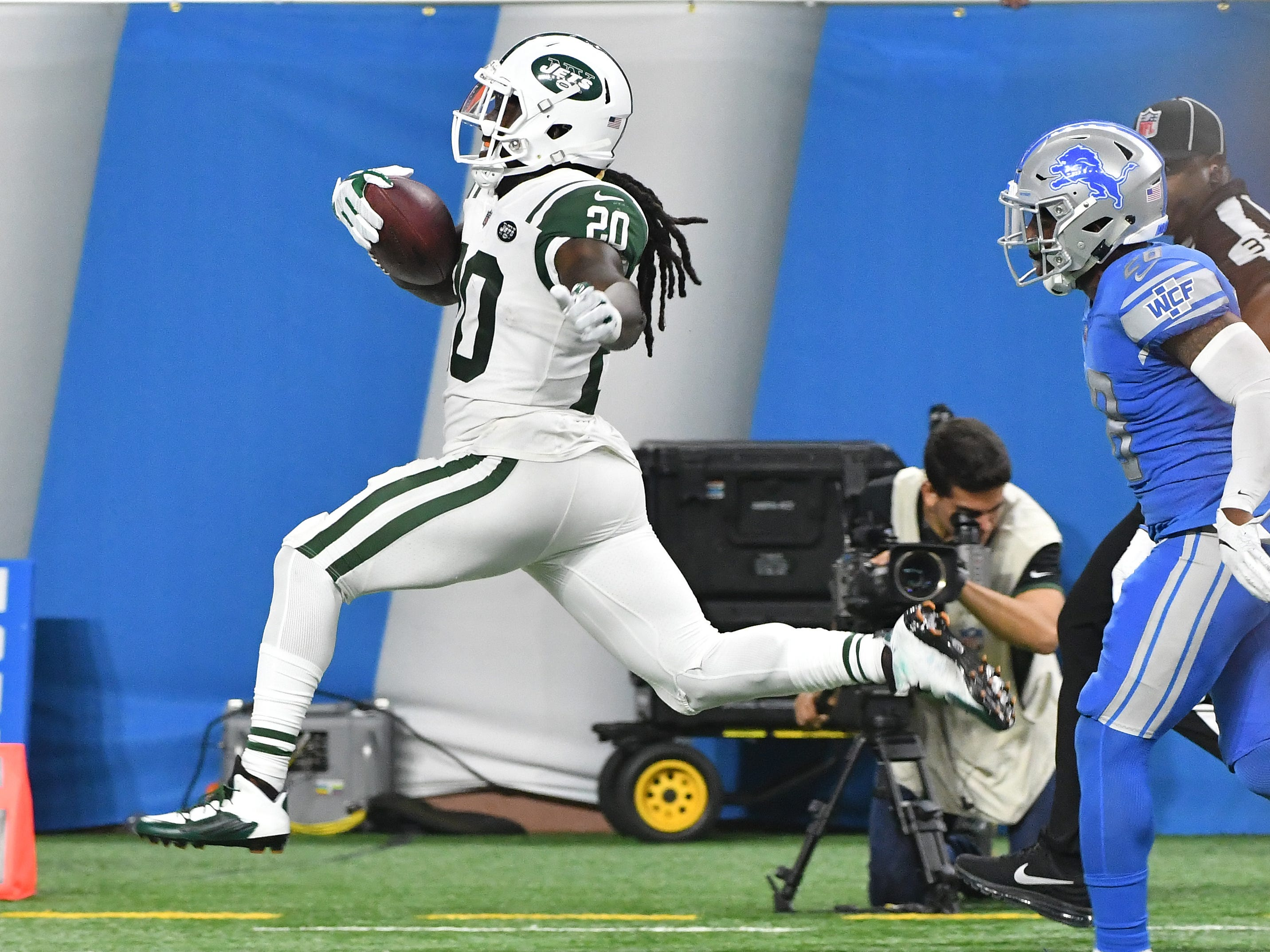 Jets' Isaiah Crowell runs a kick back for a touchdown with Lions' Quandre Diggs in pursuit in the third quarter.