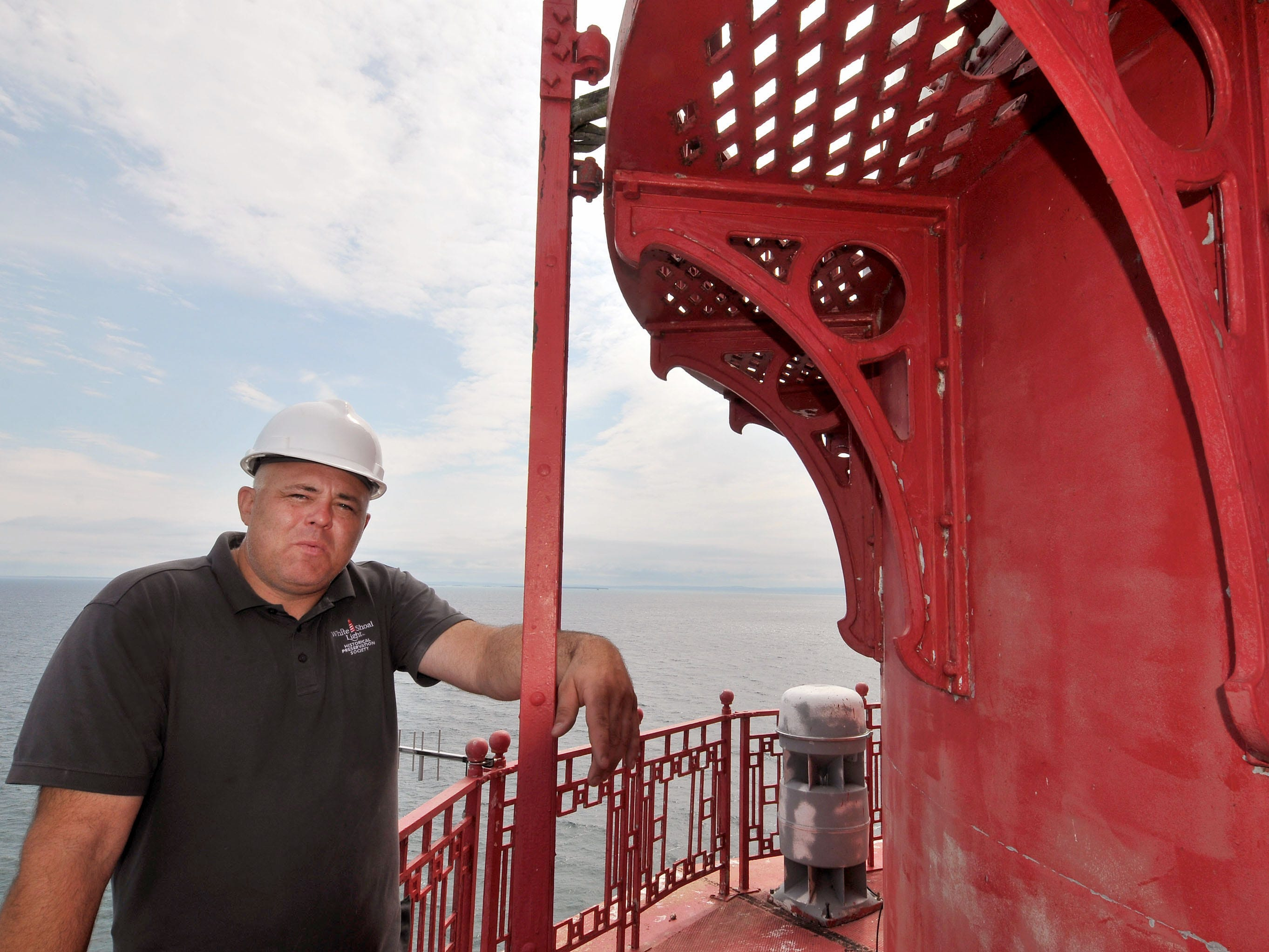 Co-owner Brent Tompkins of Traverse City stands on the catwalk at the White Shoal Lighthouse. He says this lighthouse is the only one on the Great Lakes using lightweight aluminum trim instead of cast iron.