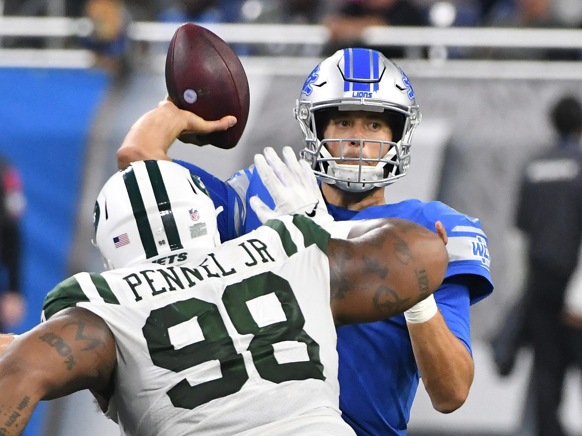 Lions quarterback Matthew Stafford throws under pressure from Jets' Mike Pennel in the fourth quarter.